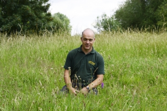 man sitting in field wildlife trust