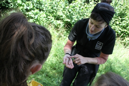 Reserve officer, Natalie, tells young nature detectives about her favourite mini beast, the worm, at Moseley Bog