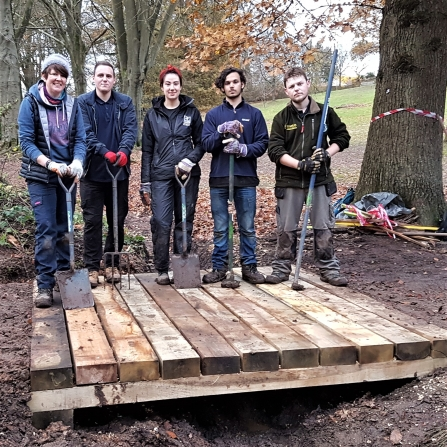 Natural Prospects trainees with the bridge they have built at Licky Hills
